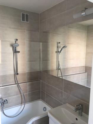 Koupelna ve světlém obkladu. Zrcadlo je vlepené do obkladu.
