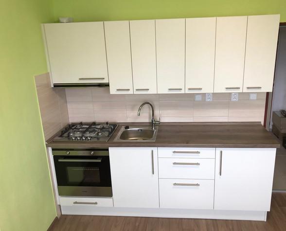 Kuchyňská linka s bílými dvířky a dřevěnou pracovní deskou.