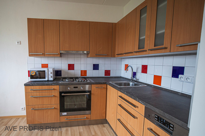 Rohová kuchyňská linka v dekoru buku, kombinace barevného obkladu Rako.
