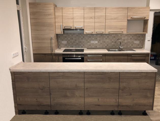 Kuchyň s ostrůvkem v rodinném doměv kombinaci dub Tabák a dub Bardolino. Obklad hnědá mozaika.