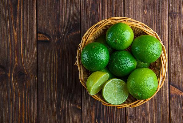 limes-wicker-basket-wooden-table-flat-la