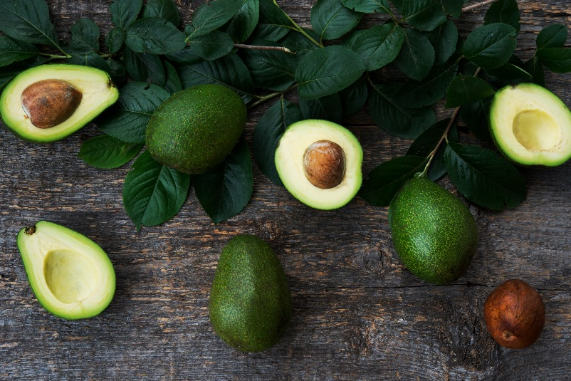 fresh-green-avocado-with-leaves-wooden-s