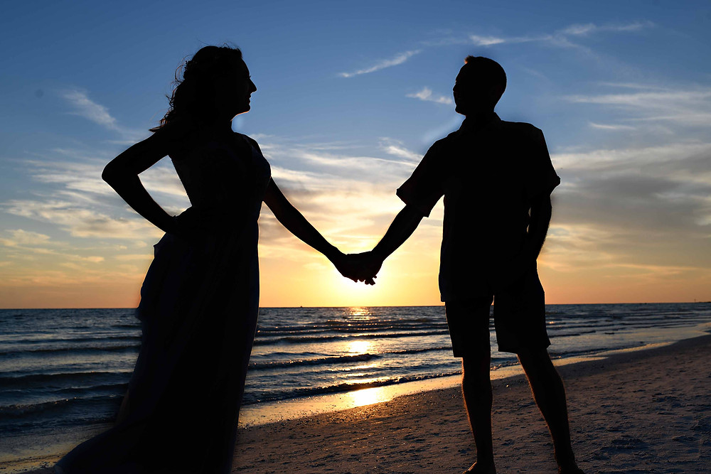 Beach wedding sunset silhouette with couple