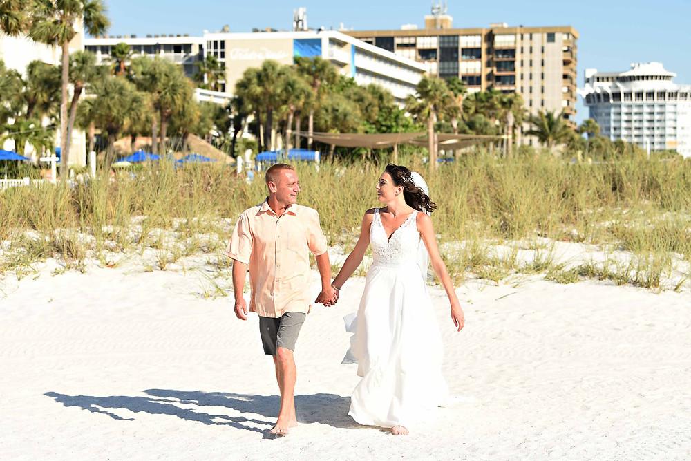 Bride and groom walking on sand dunes Beach wedding