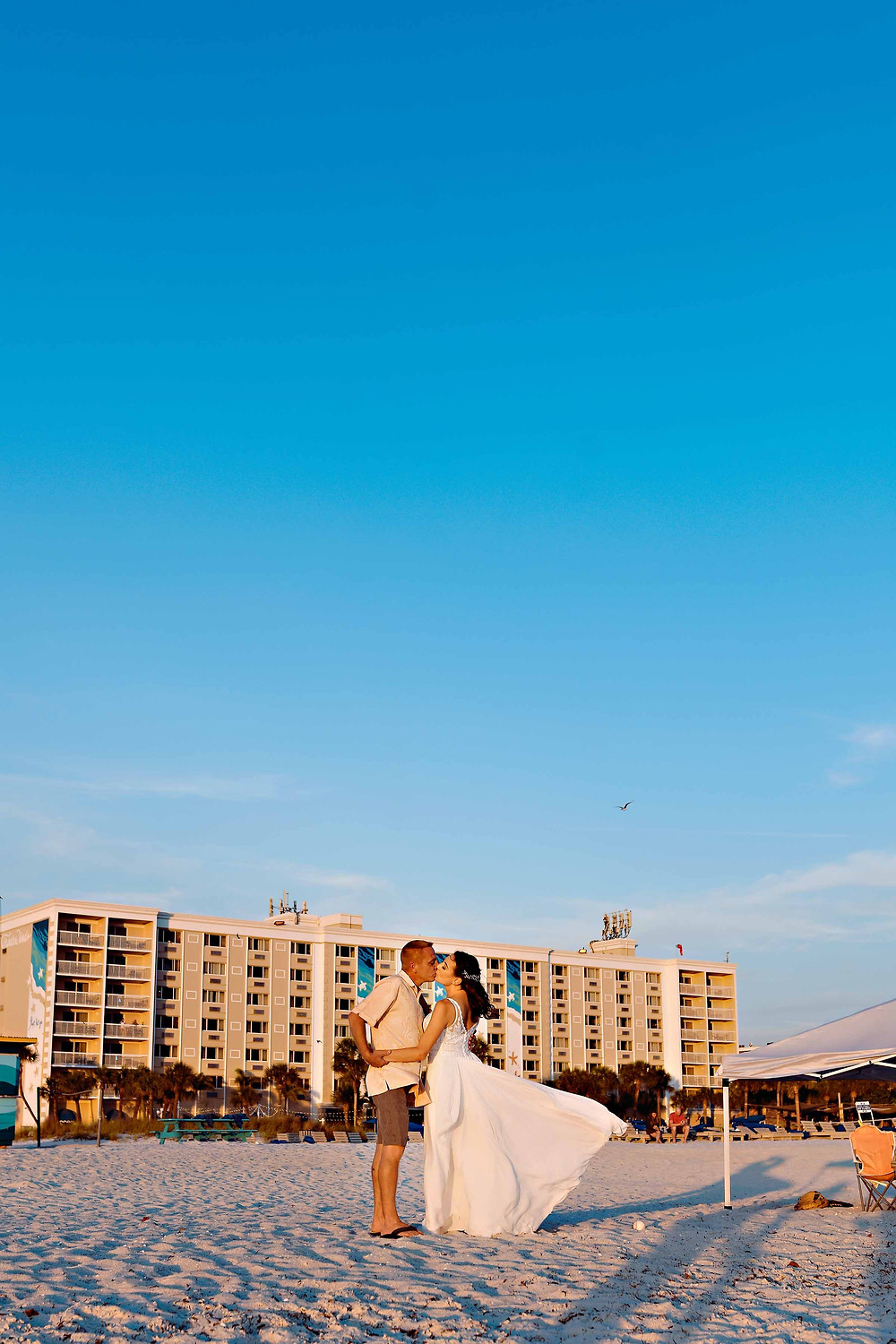 Couple dancing at sunset on the beach for their wedding