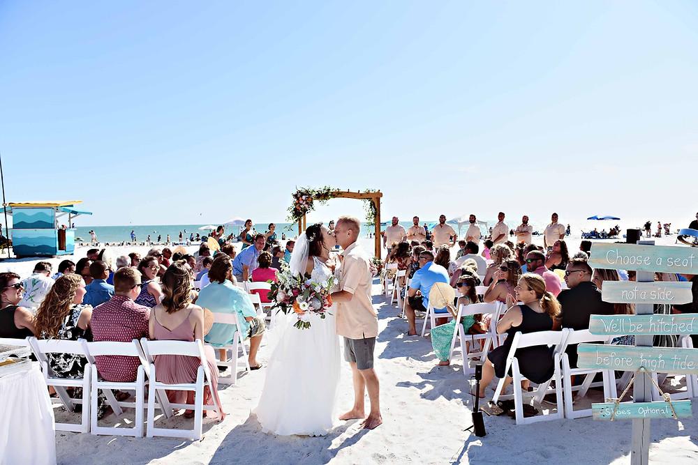 Beach wedding ceremony first kiss