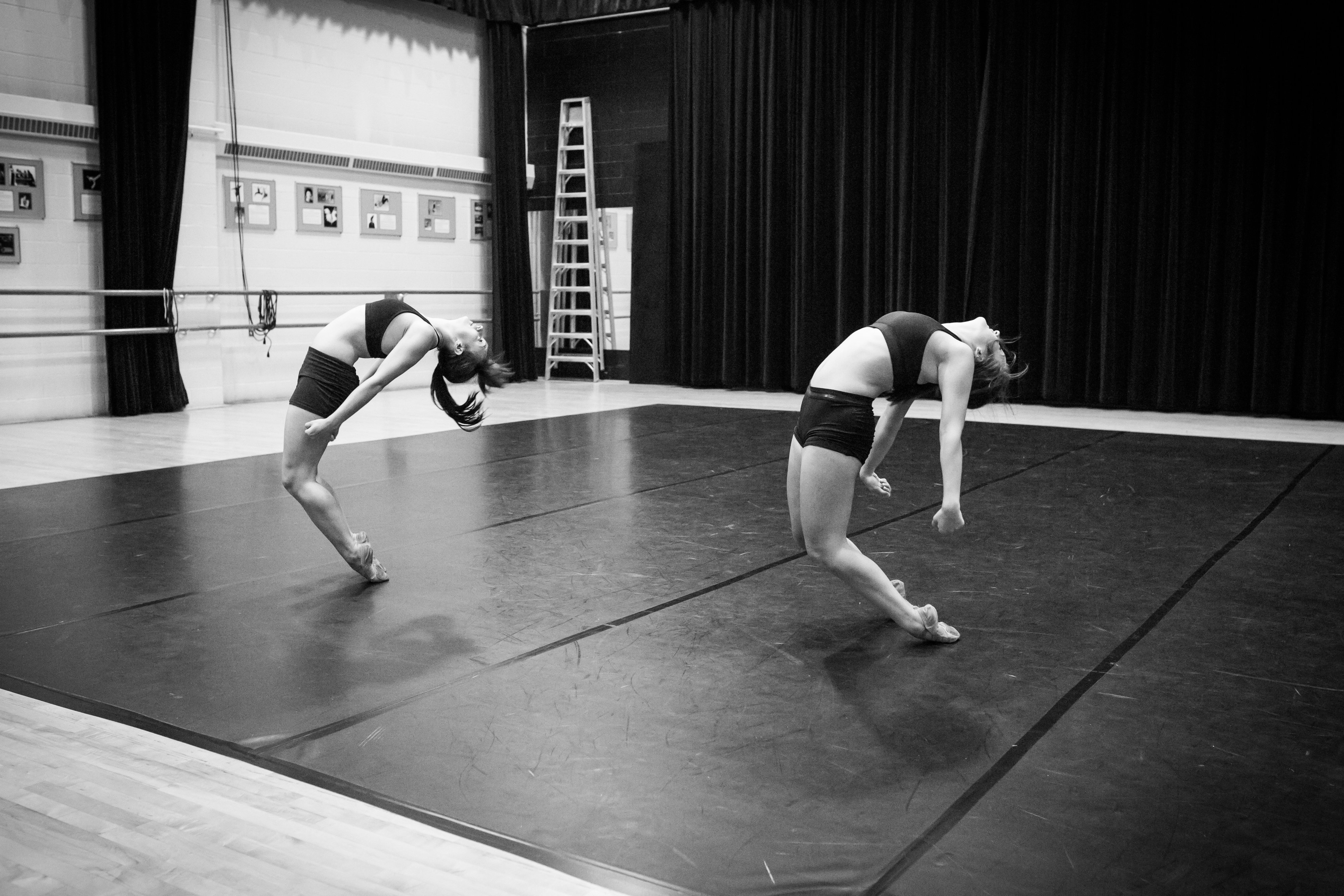 Dancers arched back in greyscale