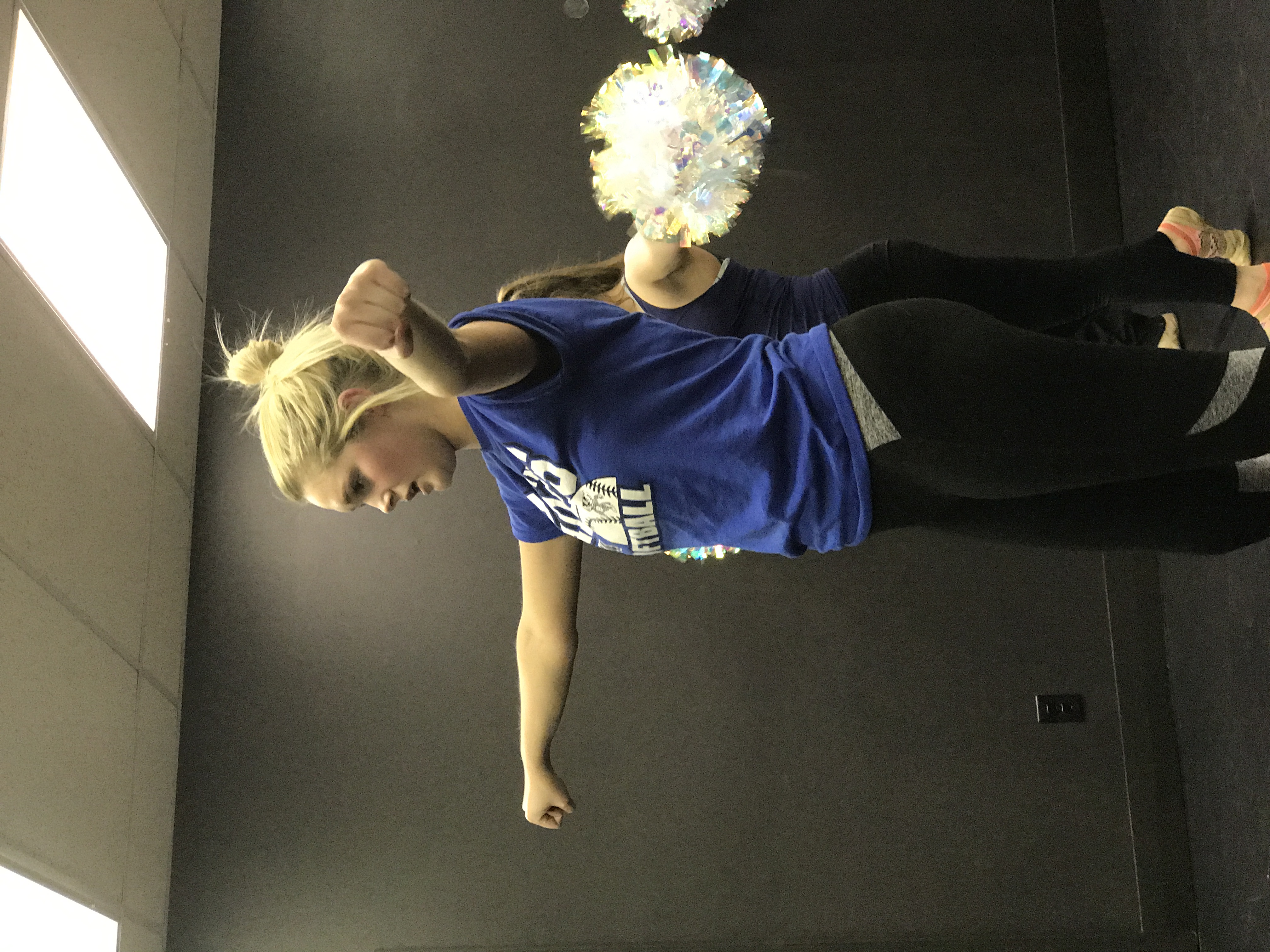 Dancer with arms spread and pompoms