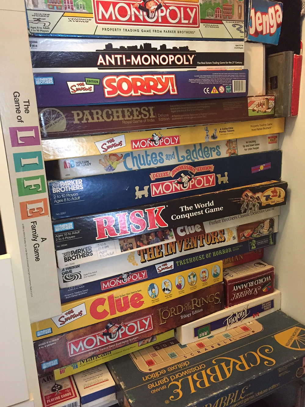 A stack of classic board games in a closet