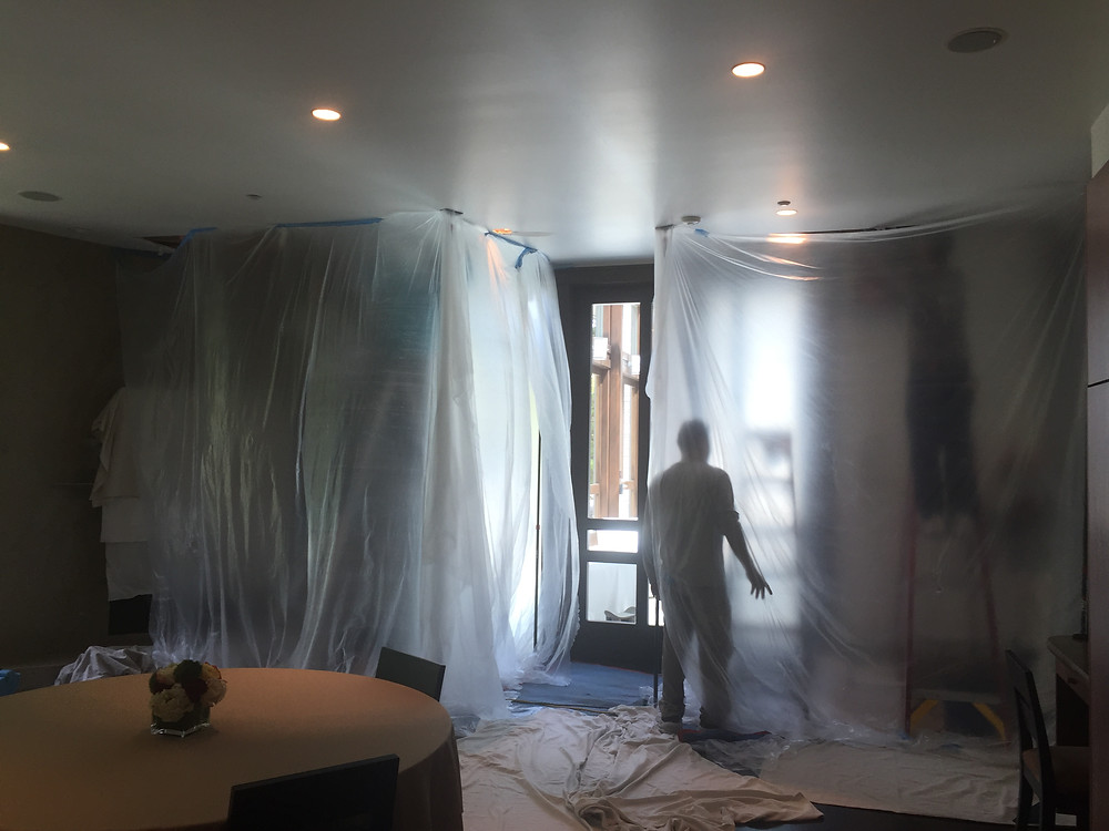Workman plastic off an area from ceiling to floor to fix a broken pipe.