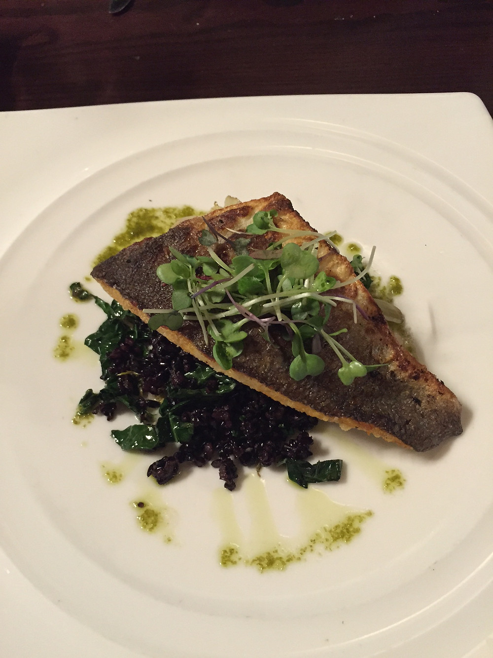 A piece of fish beautifully presented on a white dish