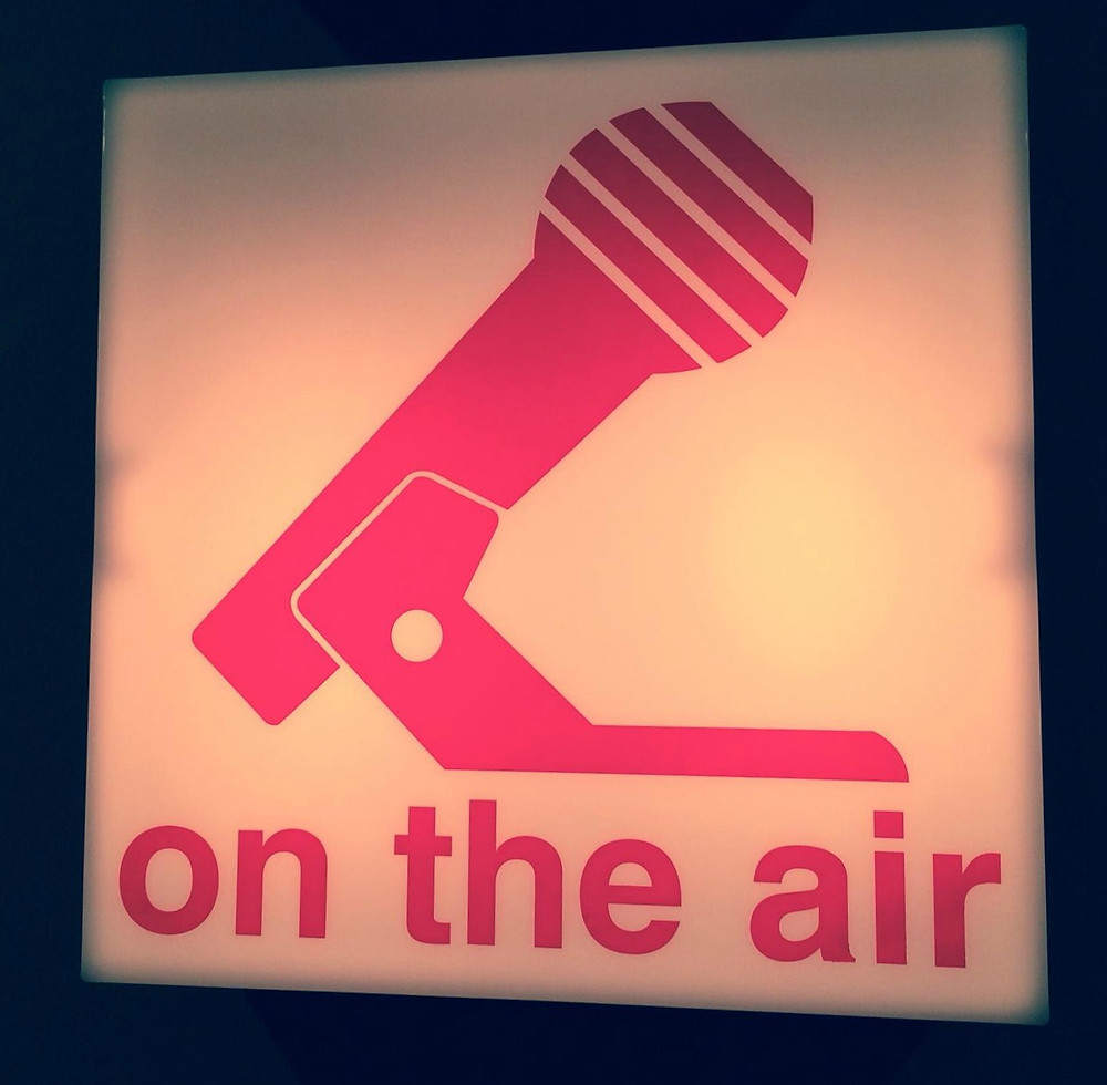 """On the Air"" sign at radio station with red microphone"