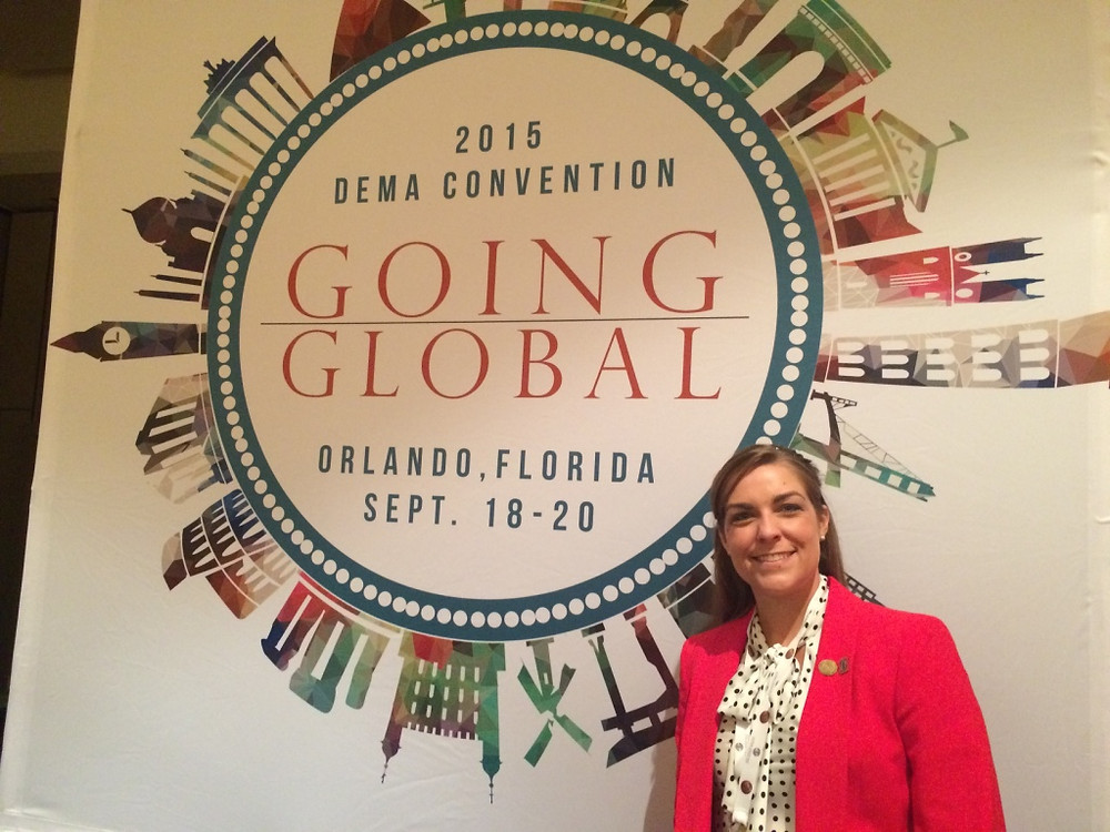 """Ms. Laurence pictured in front of conference sign """"2015 DEMA Going Global"""" in Orlando, Florida"""