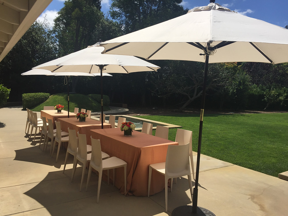 Garden party with umbrellas and a set table with flowers