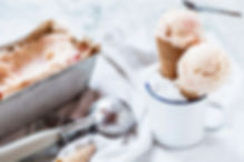 scooping homemade ice cream from tins into ice cream cones