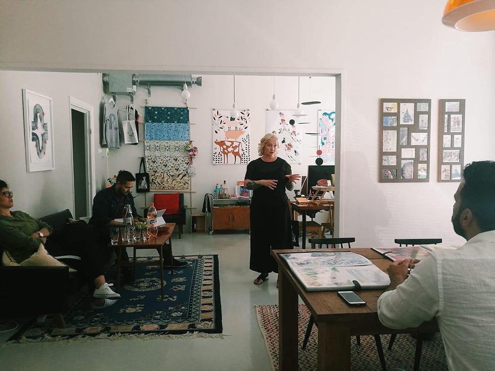 Näkymä kahdesta huoneesta, ihmisiä kahden pöydän ääressä kuuntelemassa ja kirjoittamassa muistiinpanoja, keskellä kuvaa Marjo Oliva puhumassa.