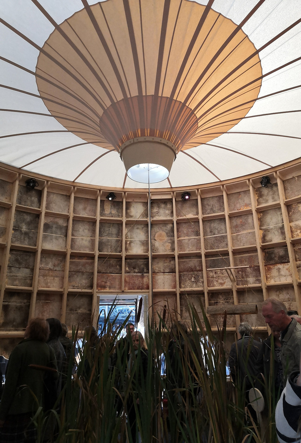 Inside of a round pavilion with central focus on the ceiling structure that looks like a wood and paper parasol