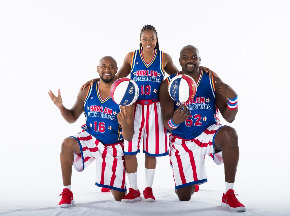 Kolme koripalloilijaa, joilla siniset paidat ja puna-valkoraidalliset shortsit. Keskimmäisenä seisoo nainen, ja hänen molemmilla puolillaan miehet, joista kummallakin sini-puna-valkoinen koripallo.
