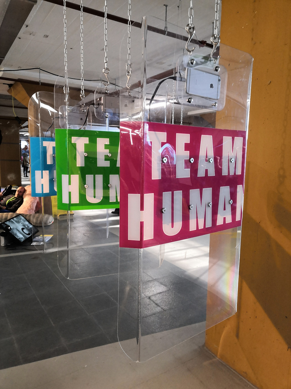 """Three clear, acrylic shields hung from the ceiling on chains, each has the text """"Team human"""" in white on a pink, green or blue background."""