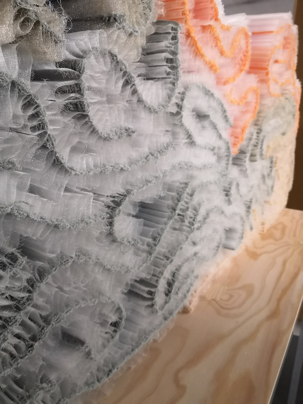 A self-supporting, 3D woven textile in grey, white and orange.