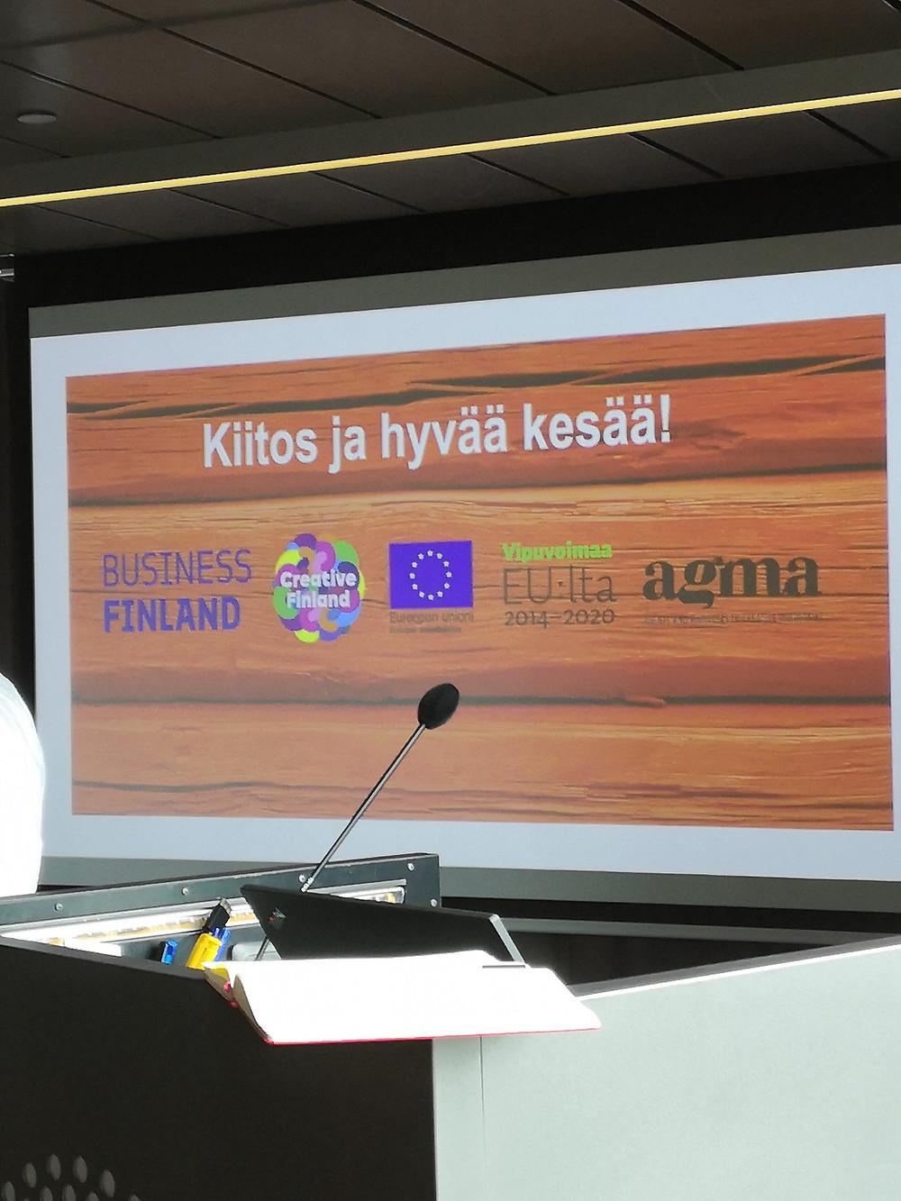"""Valkokangas, jolle heijastettu kuva punamullalla maalatusta hirsiseinästä, jonka päällä valkoinen teksti """"Kiitos ja hyvää kesää!"""" sekä Business Finlandin, Creative Finlandin, EU:n sosiaalirahaston, Vipuvoimaa EU:lta 2014-2020 ja AGMAn logot."""