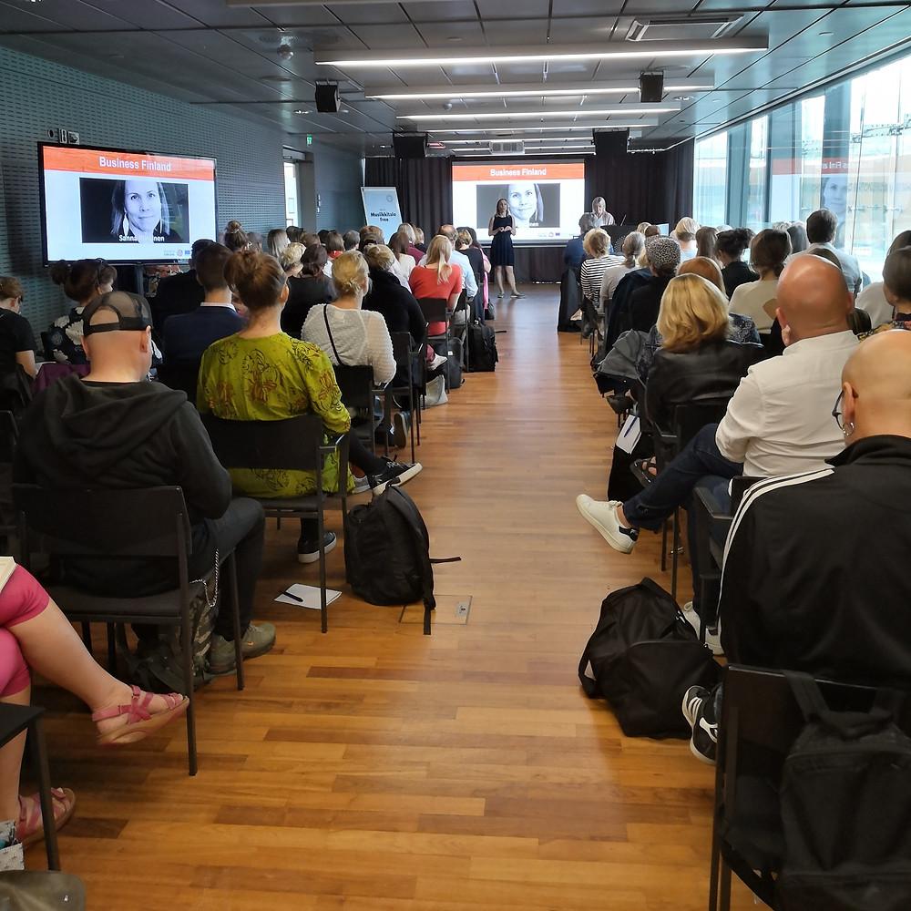 Yleisöä tuoliriveillä istumassa, kuvattuna salin takaosasta kohti salin etuosaa. Yleisön edessä nainen pitämässä puheenvuoroa.