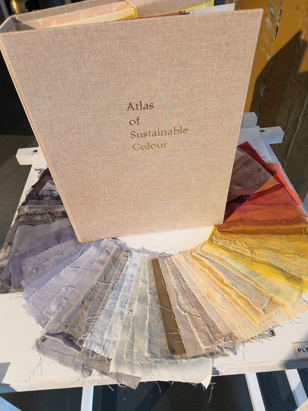 """A large book with the text """"Atlas of Sustainable Colour"""" on the cover, with different coloured swaths of cloth spread into a circle around the book."""