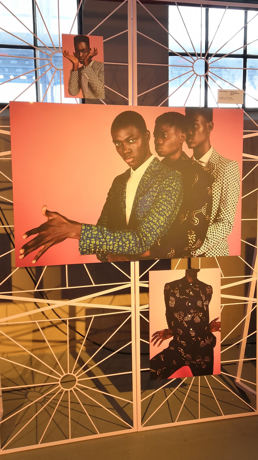 A pink metal frame holding three photos of young black men; two solo portraits and one photo with three men.