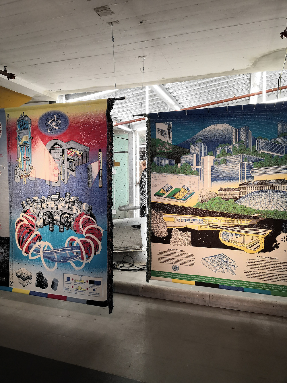 Two tapestries with woven representations of old industrial information posters.
