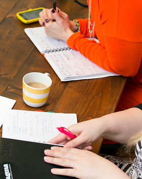 Two people at a table with calendars, notebooks and coffee cups on it.