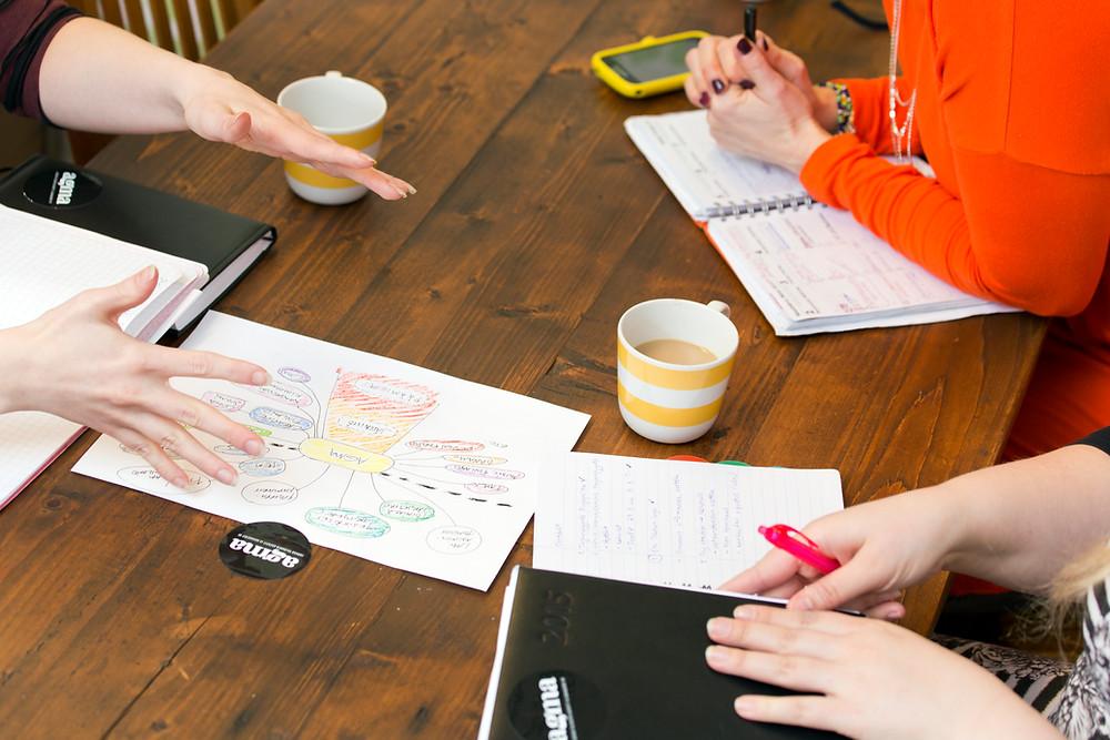 Pöytä, jolla kalentereita ja kahvikuppeja, kuvassa näkyvät kolmen, pöydän ympärillä istuvan henkilön kadet.