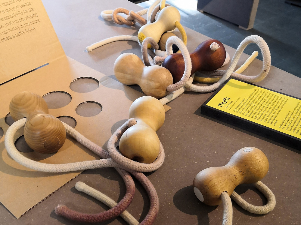 Rounded wooden shapes with soft, white ropes run through each.