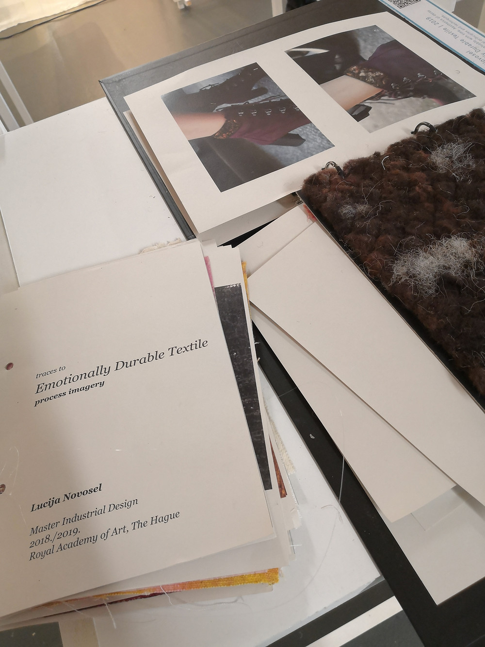 """Papers and materials on top of a table with the title """"Emotionally Durable Textile"""" visible on one of them."""