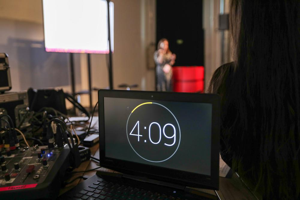 Etualalla tietokoneen näyttö, jossa näkyvillä olevassa ajastimessa aika 4:09. Taustalla epäfokuksessa henkilö esiintymislavalla.