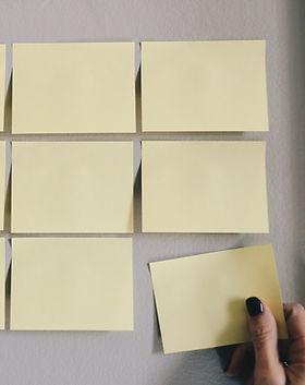 Kuusi vaaleankeltaista, tyhjää posti it -lappua vaalealla seinällä.