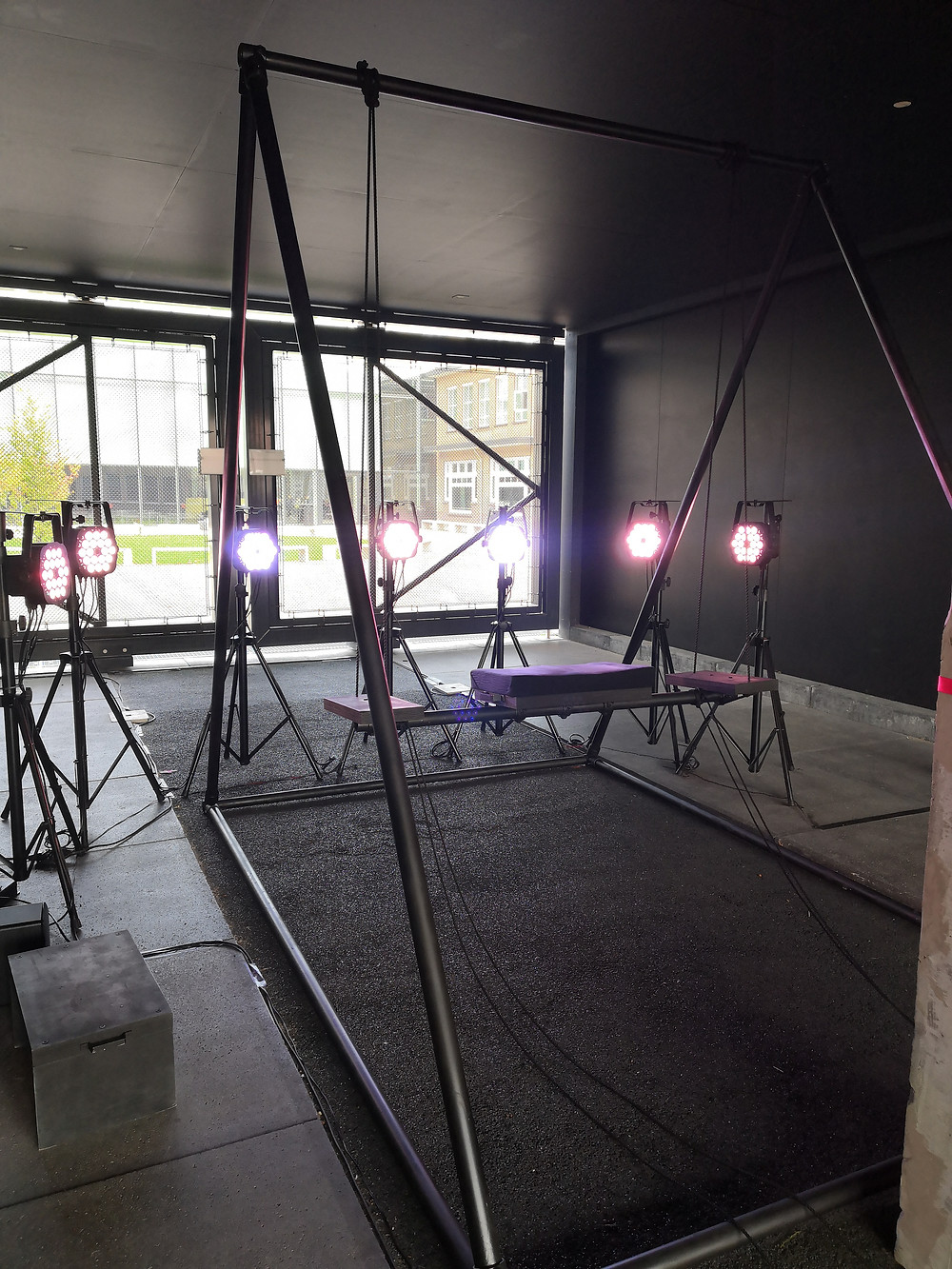 A large swing with a fram of black metal pipes stands in front of a semicircle of seven light fixtures, all aimed towards the seat of the swing