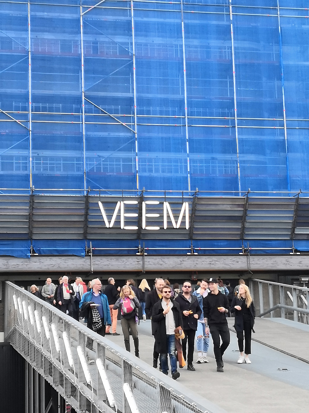 """People walking at the front of a large building mostly covered in blue material, with the text """"VEEM"""" over the entrance in lights."""