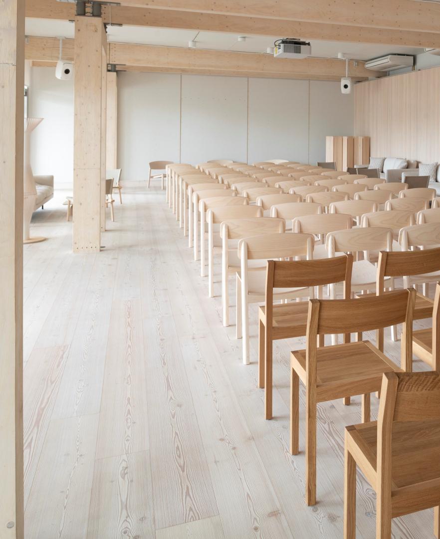 Sali, jonka pinnat ja kalusteet vaaleaa puuta, useita takaapäin kuvattuja tuolirivejä.