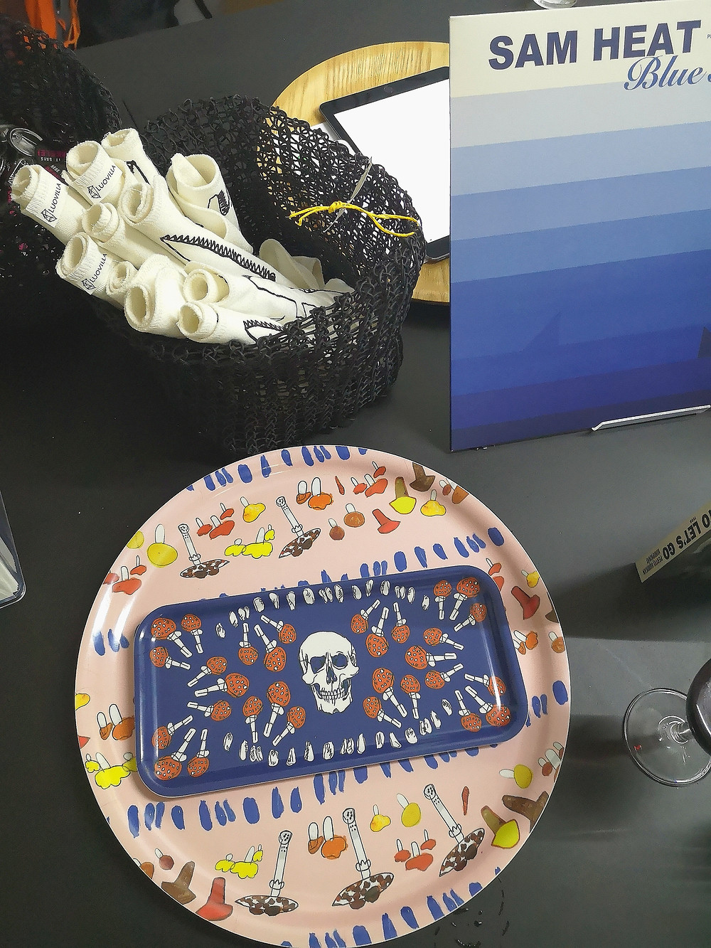 A small, black basket with rolled up black and white prints in it. At the front, two trays, one round with mushrooms on a pink background, and a smaller, blue, square tray on top of it with a skull motif.