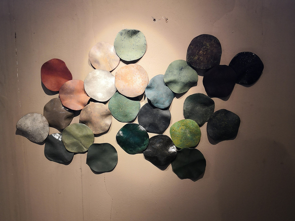 Different coloured circles cut out of a leather substitute material and arranged into a collage on a wall.