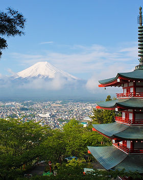 Oikealla pagodi, etualalla pensaita, joiden takaa avautuu kaupunkinäkymä ja horisontissa Fuji-vuori.
