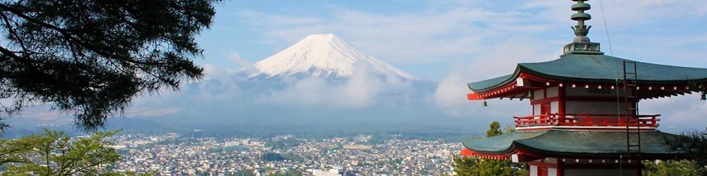 Vasemmalla männyn oksia, oikealla pagodi, näiden välistä avautuu näköala yli kaupungin kattojen, joiden takana kohoaa Fuji-vuori