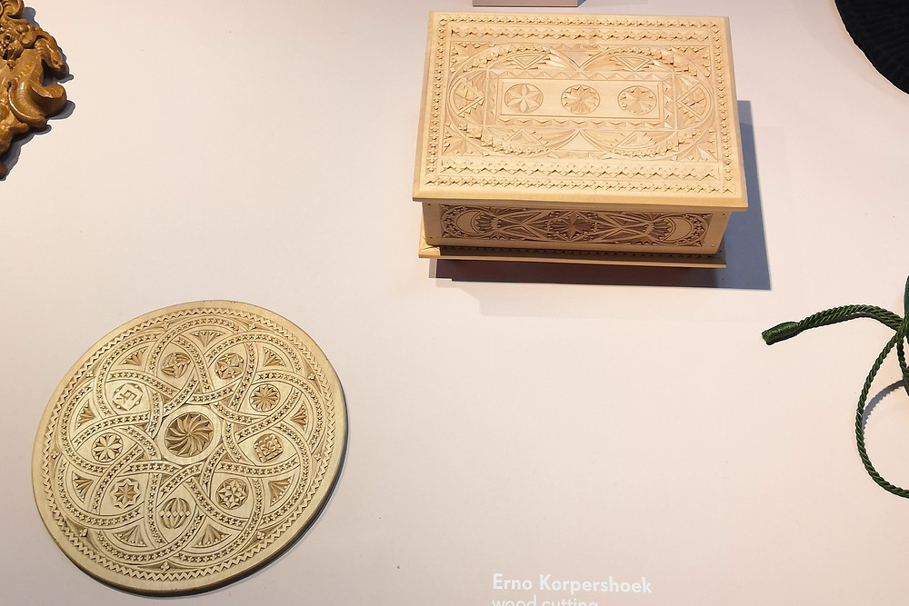 A light-coloured box and a flat round shape decorated with wood cutting