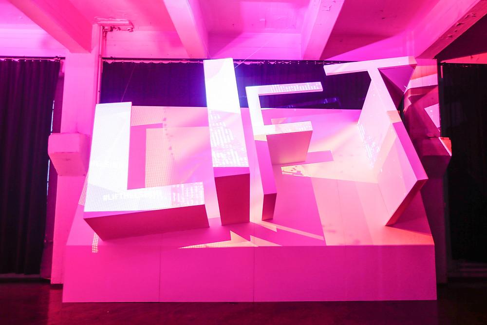 Vaaleanpunaiseksi valaistu, suuri seinäke, jossa reliefinä kirjaimet LIFT.