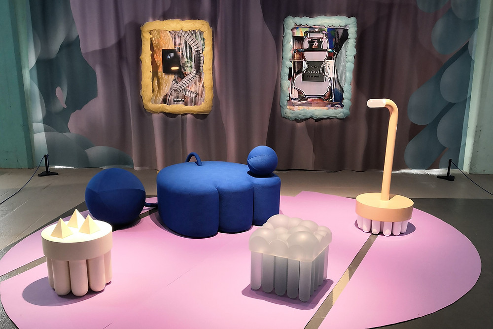 A pink circle on the floor with several pieces of pop art syle furniture on it. Two abstract paintings on the wall.