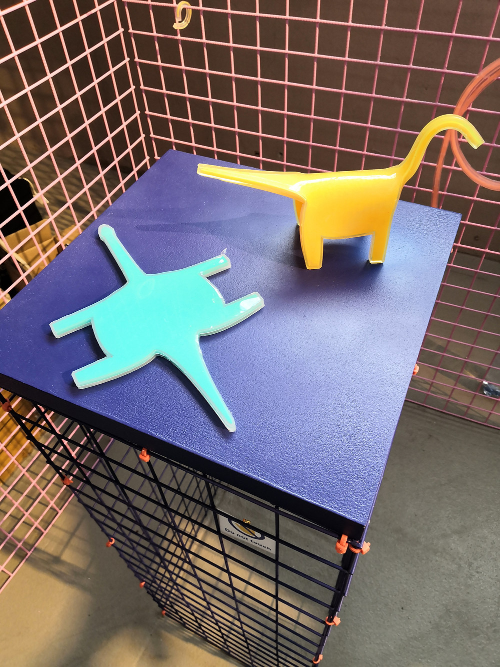 Dinosaur shapes made out of the Re-Flex material, one flat, one folded to a standing position.