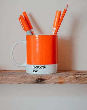 """Oranssi-valkoinen muki, jossa alareunassa mustalla teksti """"Pantone Universe 1505"""", mukin sisällä pystyssä neljä erilaista oranssisävyistä kynää."""