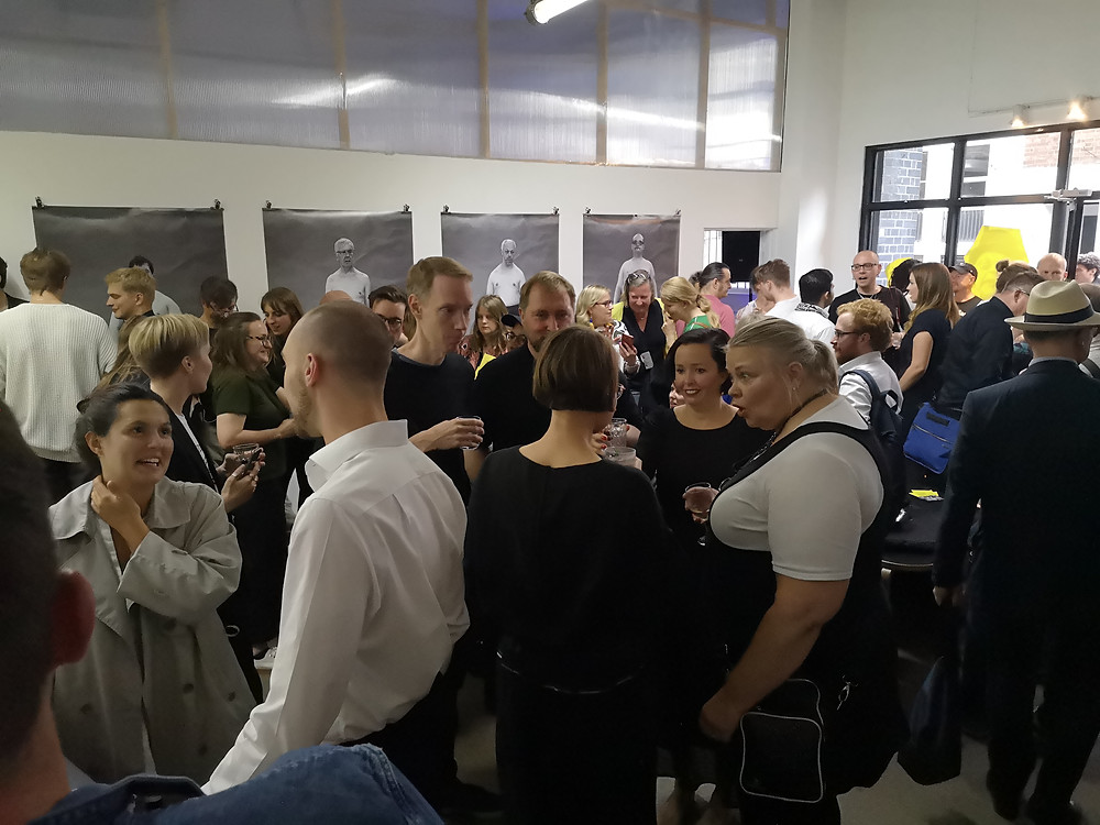 People having conversations in small groups, in the background a wall with four large, black and white photographic portraits hung on it.