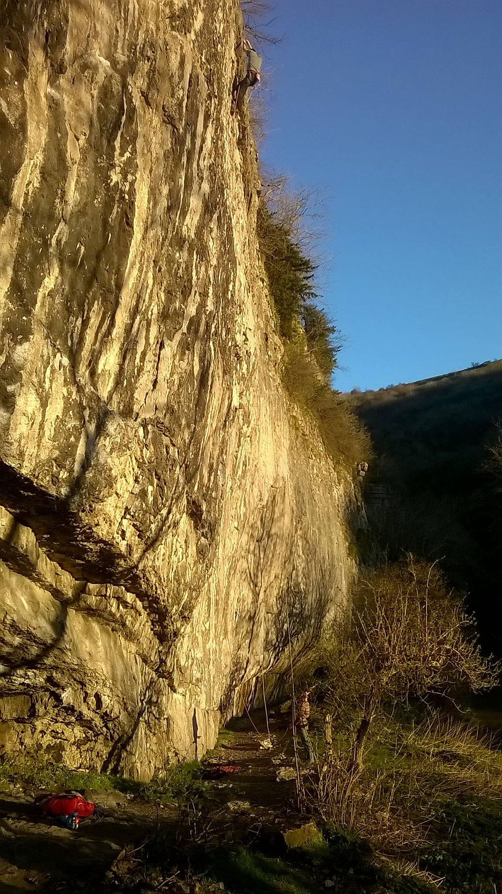 A limestone rockface in the Peak District in the evening sun. The base is dirt from teh passage of feet and the features on teh faces are covered in climber's chalk.
