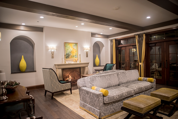 Causal space in the lobby for relaxation with a sofa, two chairs, and a fireplace.